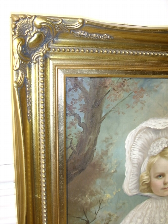 Antique 19TH.CENTURY VICTORIAN OIL ON CANVAS PORTRAIT OF A BEAUTIFUL YOUNG GIRL WEARING HER COTTON & LACE WHITE DRESS WITH BONNET TIED UNDER CHIN SEEN HOLDING FLOWERS PRESENTED IN A SWEPT GILT LATER FRAME SIZE 23.25 X 19.25 INCHES