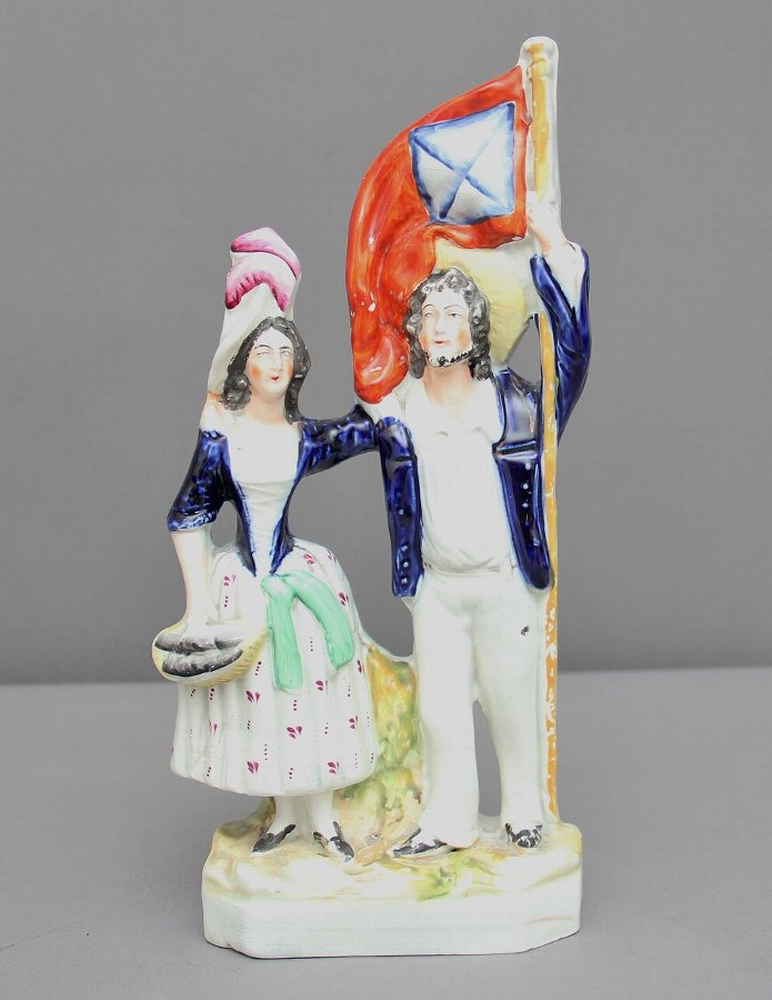 Staffordshire figure of a man holding a flag