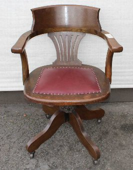 Antique 1920's Leather Oak Office chair. brown Leather Seat carved back .On castors.