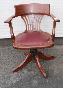 Antique 1920's Leather Oak Office chair. Leather Seat carved back . On castors.