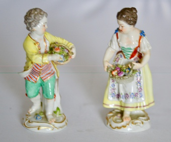 A pair of Meissen figurines of a boy and girl carrying baskets of flowers, early