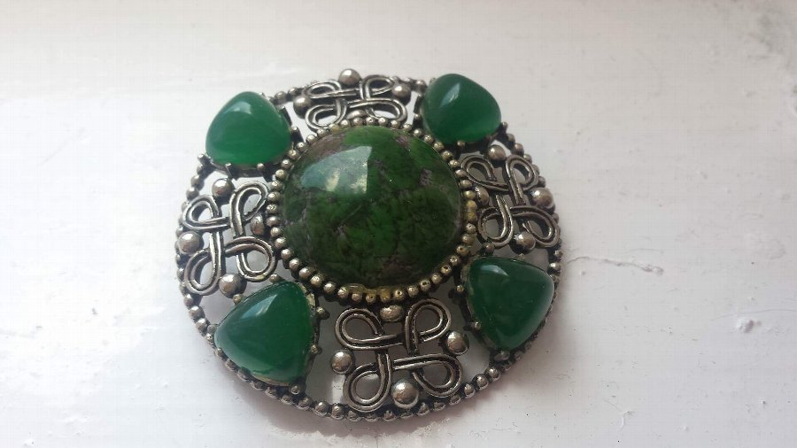 1900s celtic brooch featuring green stones