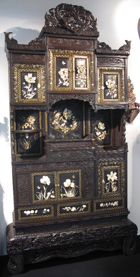 A magnificent Japanese cabinet with 13 panels including the doors, beautifully on laid with deep ivory carvings of flowers and some animals.