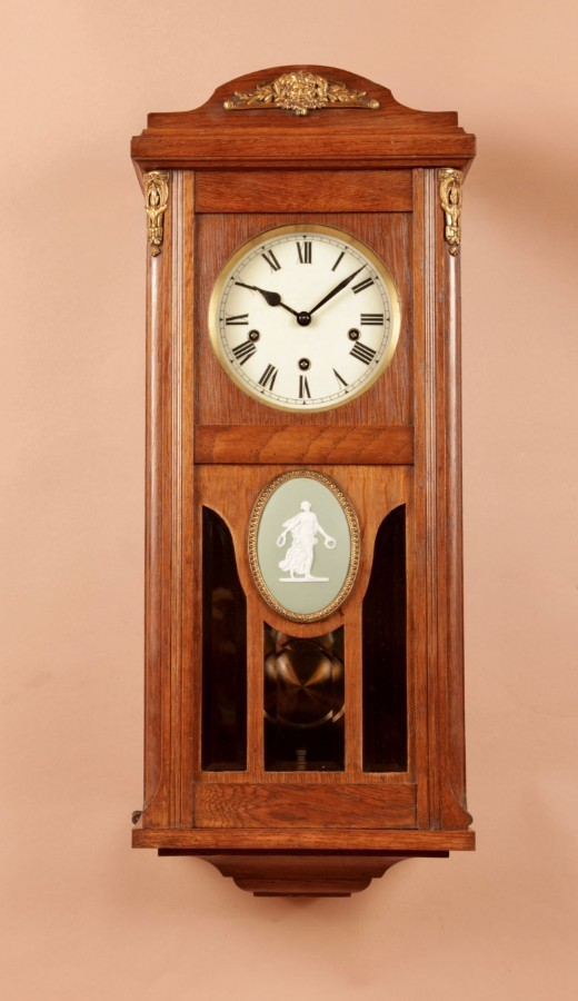 A Black Forest Arts and Craft Oak Very Stylish Wall Clock With Jasper ware Plaque.