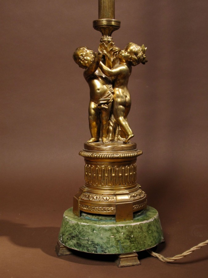 Antique A very decorative and unusual gilded bronze standard lamp with three cherubs on a simulated green marble base.