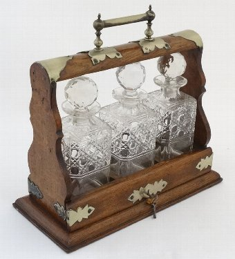 Antique Tantalus : an oak and silver plate 3 glass decante