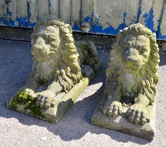 Antique Pair of composition  stone lions couchant on rectangular bases, 80cm long