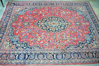 Antique North-Eastern Persia, Meshed, red ground carpet with a central blue ground medallion, 347cm x 247cm