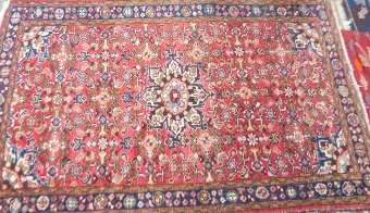 Antique Persian type red ground rug with multiple borders the centre with a shaped medallion 150cm x 105cm