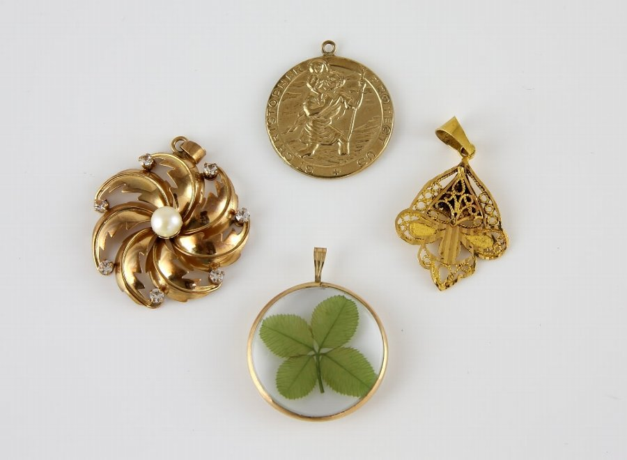 Four pendants, pearl and paste floral twist pendants in yellow metal stamped 18 ct, measuring approximately 3.5 x 3cm , with a wire work pendant in yellow metal testing as 18 ct, St Christopher pendan