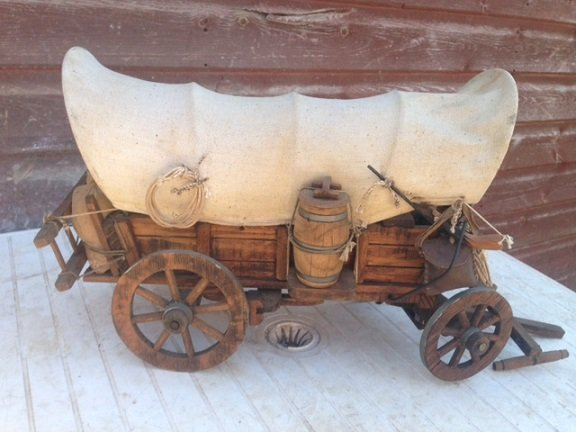 35cm long by 25cm high by 18cm width 20th century wooden model of a 19th century American wild-west canvas covered wagon.
