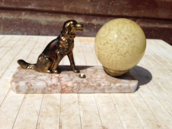 Antique A 24cm high by 14cm in depth French Art-deco, marble based side-table lamp with bronze coloured spelter figure of a dog, sitting next to a beige coloured globe