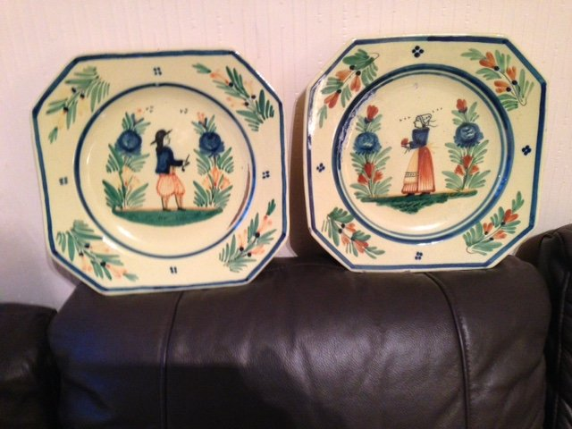 A pair of early 19th century French Quimper 25cm ceramic plates, one depicts a male figure the other a female.