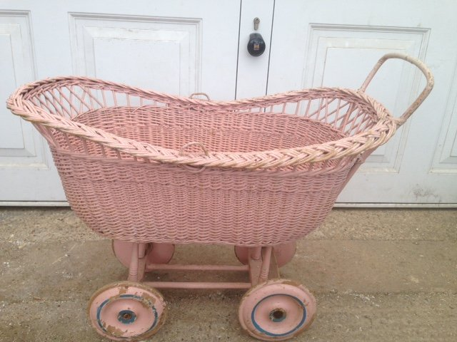 An attractive mid-20th century pink painted wickerwork dolls pram