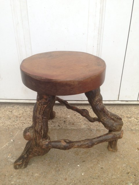 A skilfully crafted and quite unusual early 20th century solid round topped wooden stool with vine root legs.