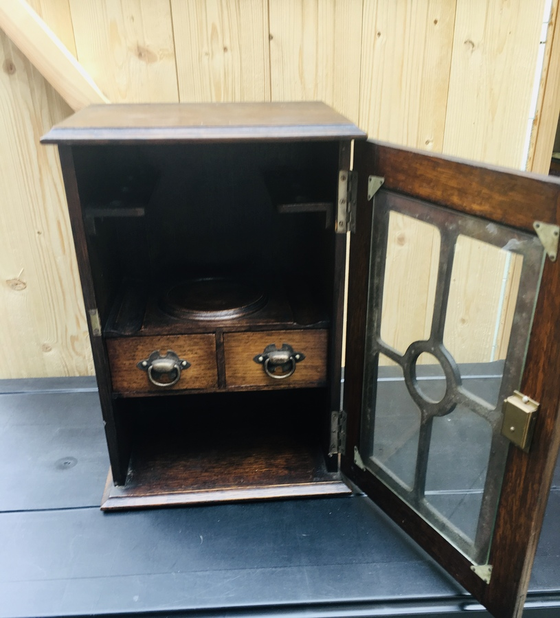 Antique An early 20th Century oak glazed smokers cabinet.