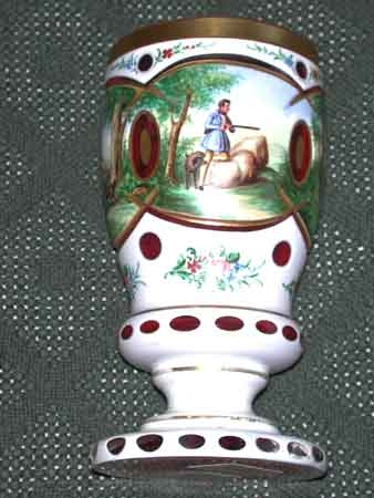 A Ruby flash and white overlay cut and enammelled goblet 20th century probably Czechslovakia painted with contiuous scenes of hunters