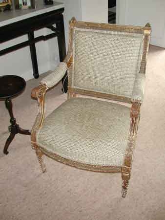 A pair of 19th century fauteuils with carved stiff leaf arms and gilded frame work.