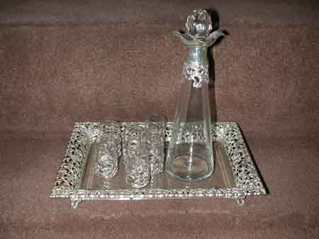 A Victorian composed liquer set somprising of a spreading cylindrical decanter with prismatic stopper, six glasses, a rectangular tray, the mounts and the border pierced and embossed with cherubic masks, fanciful birds and foliate scrolls the tray with a bevelled glass field, cartouche shaped scroll cast feet. Inscribed Sunshine Middlewood Polo Cup, 1900 Silver marked John and Wiliam Deaken Chester and Birmingham 1897